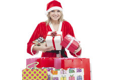 Young woman with Santa hat holding gift boxes and shopping bags Stock Photography