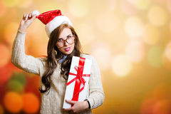 Young woman in Santa hat holding giftbox on bokeh Stock Photo