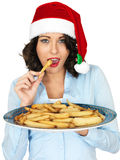 Young Woman in Santa Hat Holding a Plate of Roast Parsnips Stock Image
