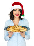 Young Woman in Santa Hat Holding a Plate of Roast Parsnips Royalty Free Stock Image