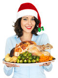 Young Woman in Santa Hat Holding Roast Turkey and Vegetables. A DSLR royalty free image, festive happy young woman housewife, with dark hair, holding a serving stock photography