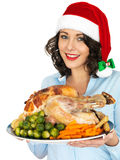 Young Woman in Santa Hat Holding Roast Turkey and Vegetables. A DSLR royalty free image, festive young happy woman smiling, with dark hair, holding a serving royalty free stock photo
