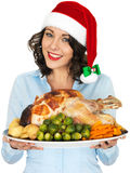 Young Woman in Santa Hat Holding Roast Turkey and Vegetables. A DSLR royalty free image, festive happy smiling young woman, holding a serving dish with a roast royalty free stock photo
