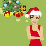 Young woman in santa hat looking up thinking about gifts under christmas tree Royalty Free Stock Image