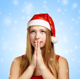 Young woman in santa hat makes a wish. Beautiful young woman in santa claus hat folds her hands in praying gesture to make a wish on blue background with falling Stock Image
