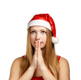 Young woman in santa hat makes a wish. Beautiful young woman in santa claus hat folds her hands in praying gesture to make a wish. Isolated on white background Stock Photo