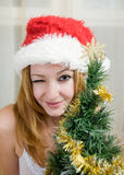 Young woman  in Santa hat near Christmas tree Royalty Free Stock Photography