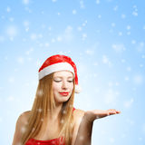 Young woman in santa hat with open hand. Beautiful young woman in santa claus hat with open hand on blue snow background Royalty Free Stock Photo