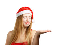 Young woman in santa hat with open hand Royalty Free Stock Image