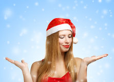 Young woman in santa hat with open hands. Beautiful young woman in santa claus hat with open hands on blue background with falling snowflakes Royalty Free Stock Photography