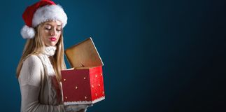 Young woman opening a Christmas gift box royalty free stock photo