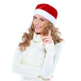 Young woman with a Santa hat pointing Royalty Free Stock Photos