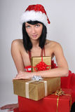 Young woman in santa hat with presents Stock Photos