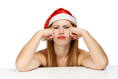 Young woman in santa hat with scowl look. Young woman in santa claus hat posing isolated on white background with scowl look Stock Photography