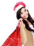 Young woman in santa hat with shopping bag. Looking at camera. isolated on white Stock Photos