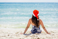 Young woman in santa hat sitting on the beach. Royalty Free Stock Images