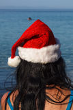 Young woman in santa hat sitting on the beach Stock Photos