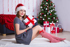 Young woman in santa hat sitting near decorated Christmas tree w Royalty Free Stock Photo