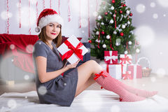 Young woman in santa hat sitting near decorated Christmas tree w Royalty Free Stock Photography