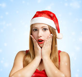 Young woman in santa hat surprised. Beautiful young woman in santa claus hat surprised on blue background with falling snowflakes Stock Photography