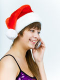 Young woman in santa hat talking on the phone Stock Images