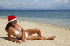 Young woman in santa hat on a tropical beach Royalty Free Stock Images