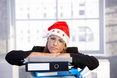 Young woman in santa hat troubled in office Royalty Free Stock Photography