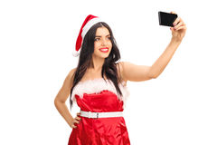 Young woman in Santa outfit taking a selfie Royalty Free Stock Photo