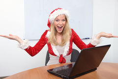 Young woman in Santa´s costume with laptop. Young woman enjoying  the Christmas atmosphere in office Royalty Free Stock Image