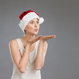 Young woman in santa's hat sending a kiss Royalty Free Stock Photos