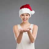 Young woman in santa's hat showing virtual product Royalty Free Stock Image