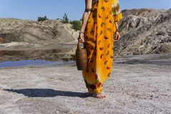 Woman goes for water. Young woman in a sari with a ceramic jar on her shoulder goes to a spring in an arid area stock photo