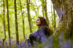 A young woman sat against a tree trunk in a field of bluebells Stock Photo