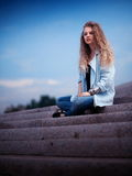 Young woman sat on steps Stock Image
