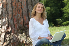 Young woman sat by tree Royalty Free Stock Image