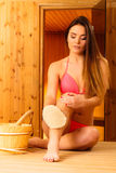 Young woman in sauna with glove Stock Photography