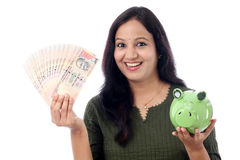 Young Woman Saves Money in Piggy bank Royalty Free Stock Images