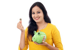 Young Woman Saves Money in Piggy bank Stock Image