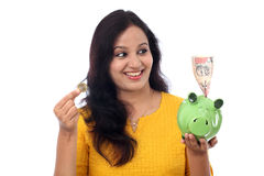 Young Woman Saves Money in Piggy bank Stock Photos