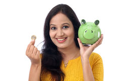Young Woman Saves Money in Piggy bank Royalty Free Stock Image