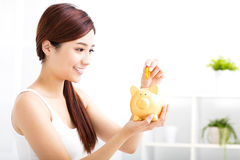 young woman saving money in the piggy bank Royalty Free Stock Photo