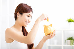 Young woman saving money in the piggy bank Stock Photos