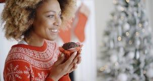 Young woman savoring a Christmas cake Stock Photography