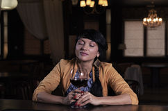 Young woman savouring a glass of red wine. As she sits at the bar counter in a nightclub with her eyes closed in enjoyment Royalty Free Stock Photography