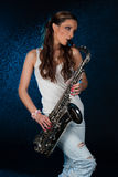 Young woman with a saxophone stock photography