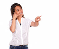 Young woman saying call me pointing to her left Royalty Free Stock Image