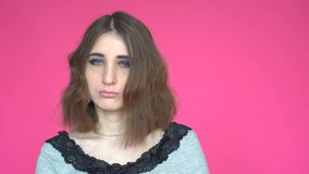 Young woman says No, by shaking her head. posing against on pink background. stock video footage
