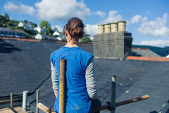 Young woman on scaffolding by roof Stock Photo
