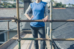 Young woman on scaffolding by roof Royalty Free Stock Image