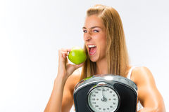 Young woman with scale under her arm and apple Royalty Free Stock Image